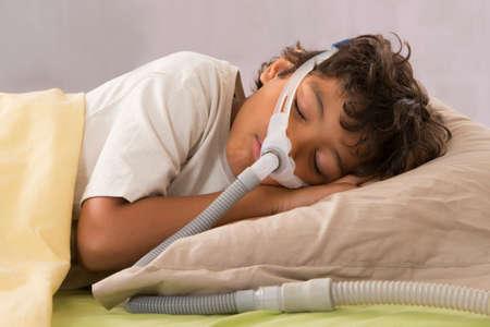 apnea: bambino che soffre di apnea del sonno, utilizzando una macchina CPAP