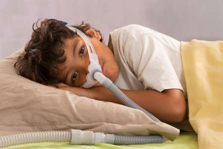 child with sleeping apnea and CPAP machine photo