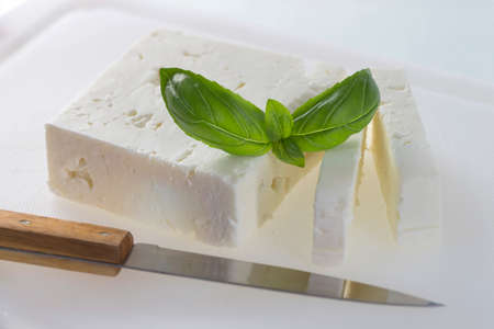 feta cheese: feta cheese cut in slices,  with basil Stock Photo