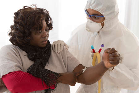 ebola: Doctor in protective follows is drawing blood from african woman to perform a test Stock Photo