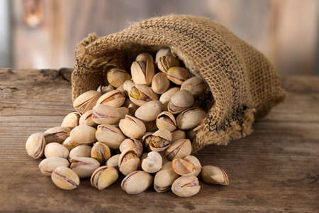 pista: roasted and salted pistachios pour out of a burlap bag