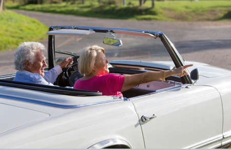 a meeting with a view to marriage: Senior couple in convertible car enjoying day trip Stock Photo