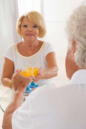 senior couple having an orange juice, break