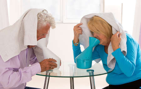 70 s: Senior couple with flu having doing inhalation together