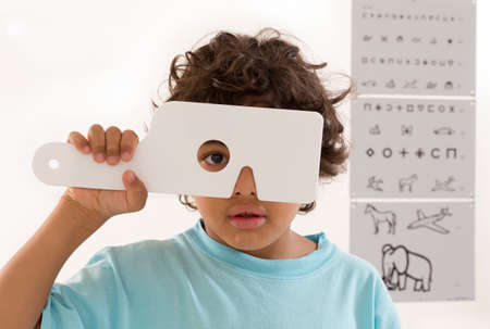 optical instrument: Young boy s eye exam HAVING Performed by optician, optometrist or eye doctor.