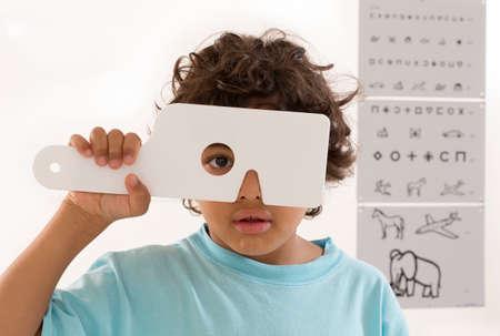 doctor of optometry: Young boy s eye exam HAVING Performed by optician, optometrist or eye doctor.