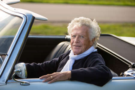 top down: Senior man in white vintage sports car