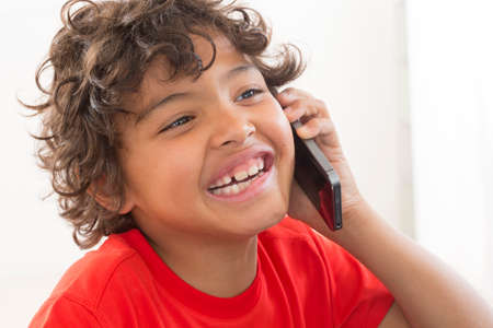 communicates: Happy smiling young boy communicates with smartphone
