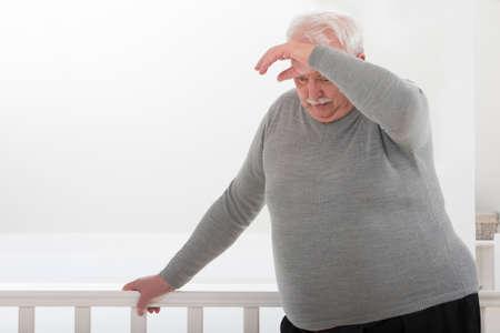 zwaarlijvige man op zoek bezorgd met de hand op het voorhoofd Stockfoto