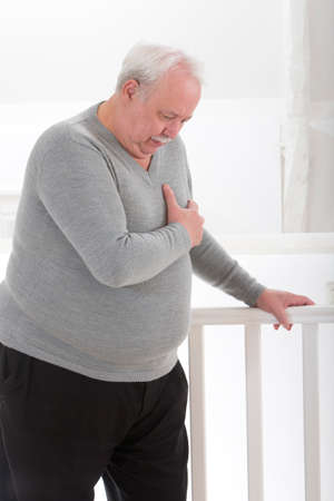 heart attack: oerweight senior man hand grabbing his  chest Stock Photo