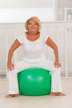 60 years: senior woman exercizing on a sport ball