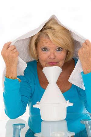 Senior woman with flu having doing inhalation