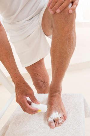 lower limb: Senior man doingmycosis treatment Stock Photo