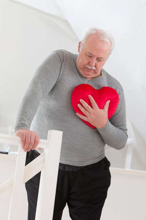tightness: Senior man holding an heart symbol of heart attack