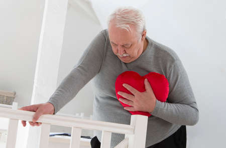 angina: Senior hombre sosteniendo un símbolo del corazón de un ataque al corazón