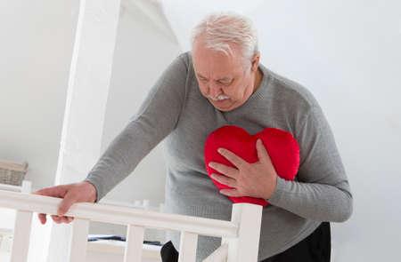 chory: Starszy mężczyzna trzyma symbol serca zawału serca