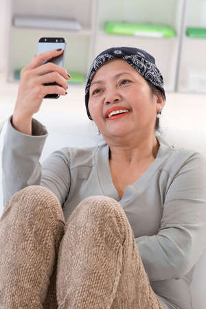 Smiling senior asian thai woman using cell phone photo