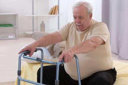 歩行車を使用して年配の男性