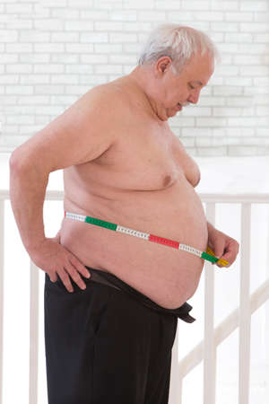 profile measurement: Doctor measuring waist to an overweight senior man Stock Photo
