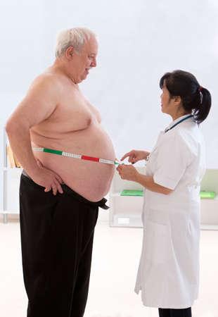 obeso: obesidad medida de la cintura del hombre mayor Foto de archivo