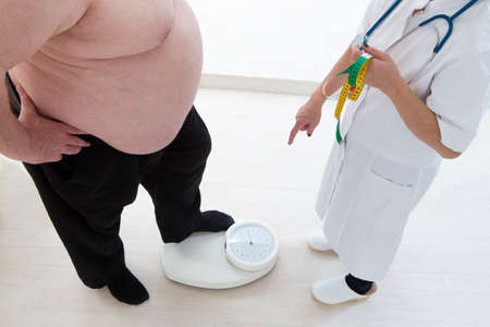 profile measurement: Overweight senior man measuring His weight with doctor