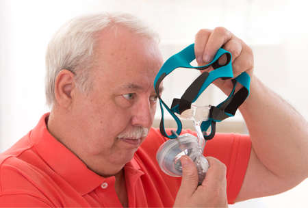 sleep mask: Senior Man with sleeping apnea and CPAP machine