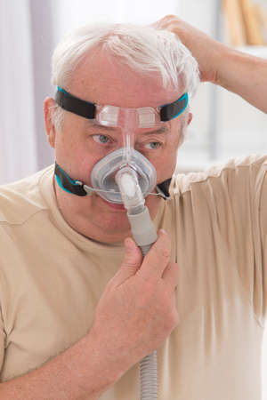humidifier: Senior Man with sleeping apnea and CPAP machine