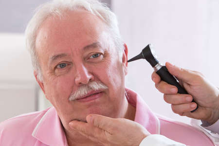 otoscope: Doctor using otoscope to look in a senior man
