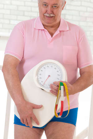 profile measurement: Overweight  senior man measuring his weight with doctor Stock Photo