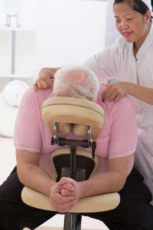 massage chair: overweight man having massage in a massage chair
