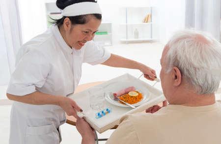 Senior wman eet lunch in bejaardentehuis (zorg, thuis, ouderen) Stockfoto