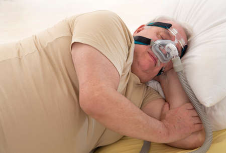 Senior Man with sleeping apnea and CPAP machine