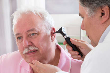 physical exam: Doctor using otoscope to look in a senior man
