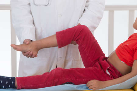 lower limb: Doctor examining boy leg because of knee problem symptoms Stock Photo