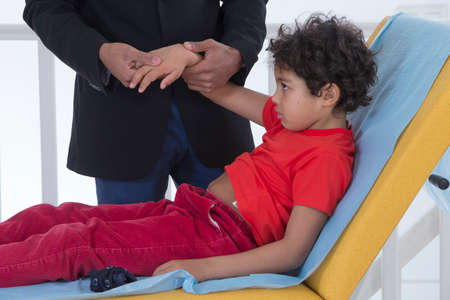 3 year old boy: Doctor checking boy  wrist because of pain Stock Photo