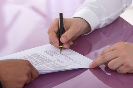 lawsuit: Detail of a man signing a paper Male finger showing where to sign