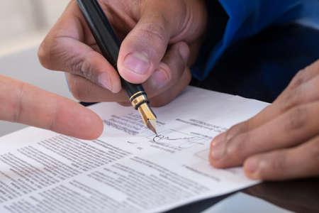 contratos: Detalle de un hombre que firma un documento dedo masculino que muestra d�nde firmar