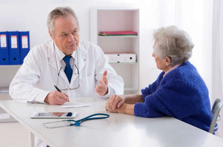 elderly pain: Doctor talking to his female senior patient at the office
