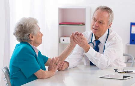 codo: Doctor que controla el brazo lesionado del paciente anciano Foto de archivo