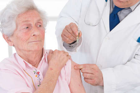 medicalcare: Doctor injecting vaccine to senior woman