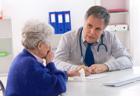 consultation woman: doctor explaining diagnosis to His female patient Stock Photo