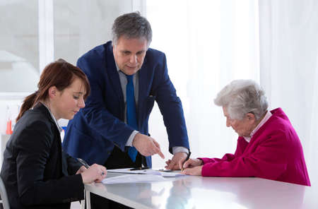 grand daughter: Grand mother signing insurance contract and donation to her grand daughter Stock Photo
