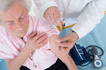 flu vaccine: Doctor injecting vaccine to senior woman