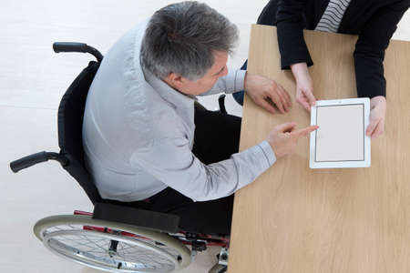 paraplegico: Hombre de negocios en silla de ruedas con su asistente personal en la oficina