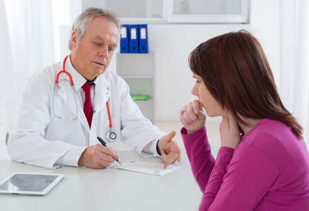 Doctor talking to His young female patient at the office Imagens
