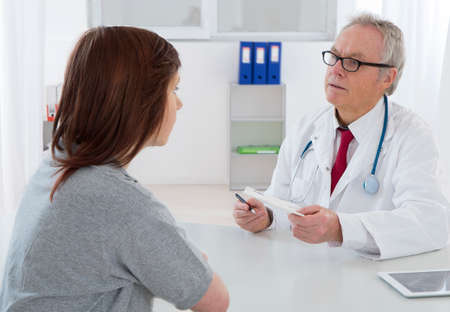 Doctor talking to His young female patient at the office
