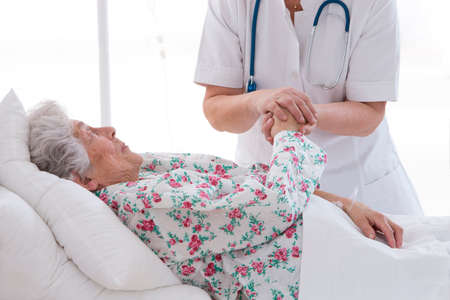 medical doctor holding senior patients hands and comforting her photo