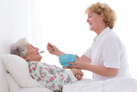 Nurse feeding an elderly woman atretirement house, or hospital Stock Photo