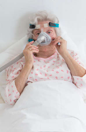 respiratory tract: elderly woman adjusting her CPAP machine Stock Photo