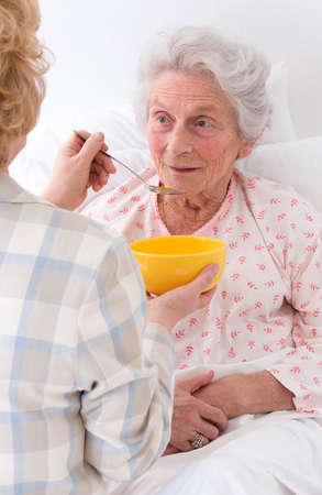 elderlycare  feeding an elderly woman atretirement house, or home
